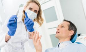 female general dentist discusses with her patient