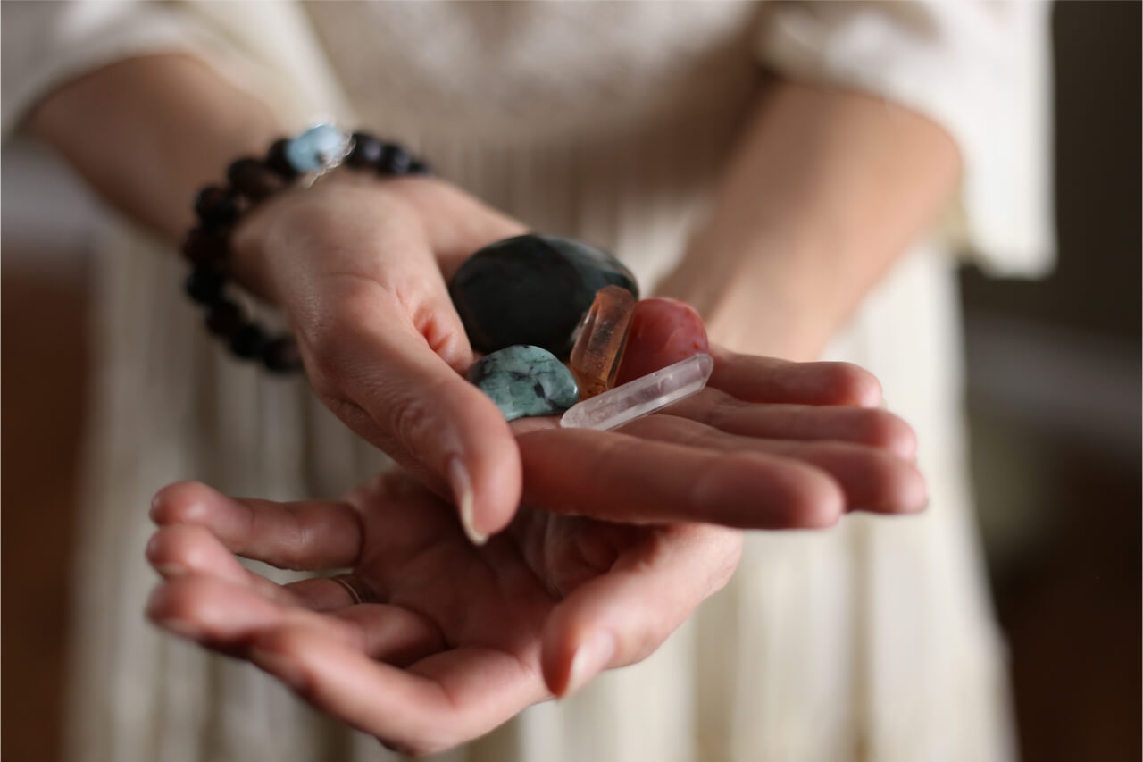 The woman is holding various healing crystals.
